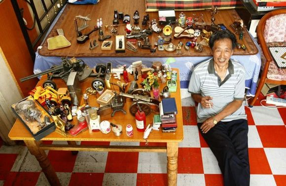 chinese pensioner, cui you near his lighet collection